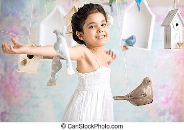 Joyful girl among wooden birds