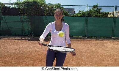 Joyful girl balancing ball on tennis racket at tennis court