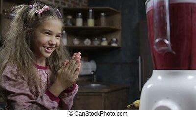 Joyful girl blending berry smoothie in the kitchen