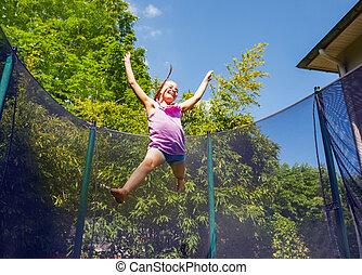 Joyful girl bouncing around a trampoline outdoors