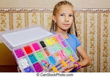 Joyful girl holding a set of weaving