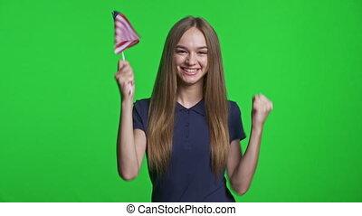 Joyful girl holding small USA flag celebrating triumph, over...