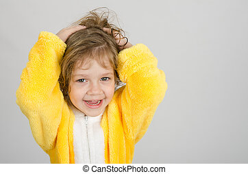 Joyful girl in a yellow bathrobe