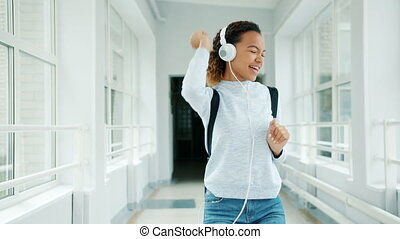 Joyful girl in headphones having fun in university hall singing dancing