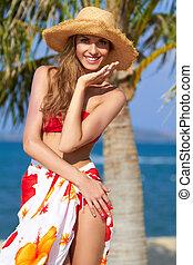 Joyful girl in red bikini posing at the beach