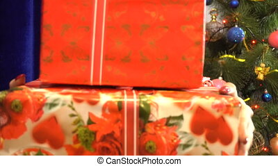 joyful girl in santa hat hides behind a christmas gifts