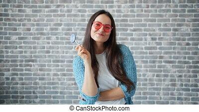 Joyful girl in sunglasses holding lollipop smiling on brick...