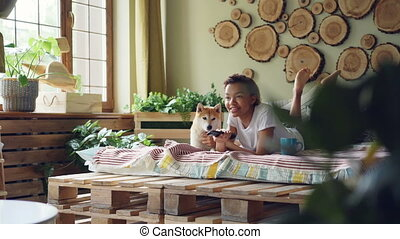 Joyful girl is watching TV with her cute puppy holding...