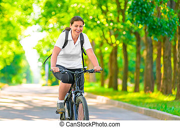 Joyful girl on a bicycle with a backpack