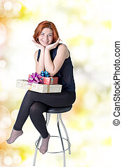 Joyful girl on a chair with gifts
