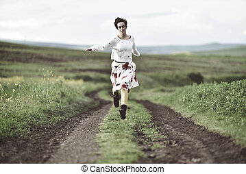 Joyful girl running on a countryside road