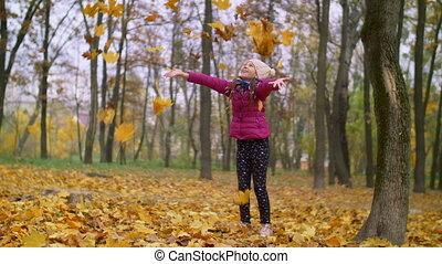 Joyful girl tossing autumn foliage up outdoors - Joyful...