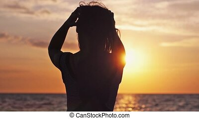 Joyful girl with long hair standing with arms wide spread...