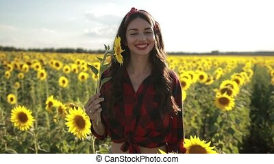 Joyful girl with sunflower enjoying nature