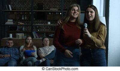 Joyful girls singing karaoke in domestic room - Cheerful...