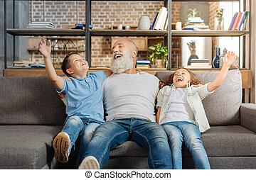 Joyful grandfather and his grandchildren laughing on sofa