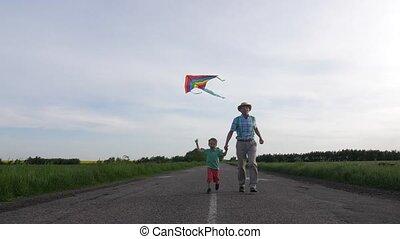 Joyful grandpa with grandson flying kite outdoor - Cheerful...