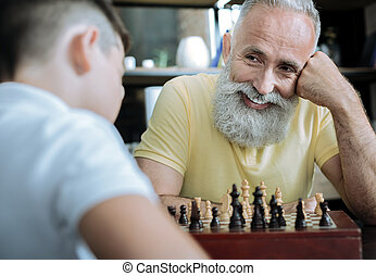 Joyful grandparent beaming while playing chess with kid