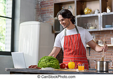 Joyful guy preparing food in kitchen
