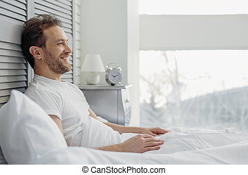Joyful guy relaxing in bedroom