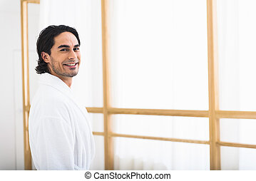 Joyful guy relaxing in spa robe