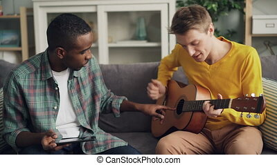 Joyful guys African American and Caucasian friends are playing the guitar, using tablet and laughing relaxing on sofa together in modern apartment. Friendship and music concept.