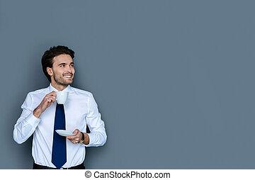 Joyful handsome man enjoying coffee