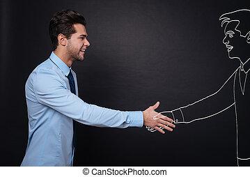 Joyful handsome man shaking hands with work partner.