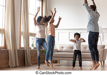 Joyful happy african family having fun jumping at home together