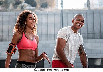 Joyful happy couple enjoying working out together