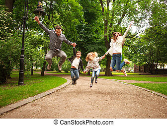 Joyful happy family in summer park together jumping have fun