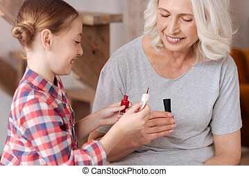 Joyful happy girl holding a nail varnish brush