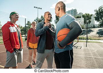 Joyful happy man greeting his basketball coach