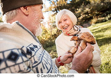 Joyful happy man showing mushrooms to his wife