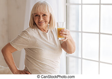 Joyful happy woman holding a glass with orange juice