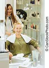 Joyful happy woman looking at her hairdresser