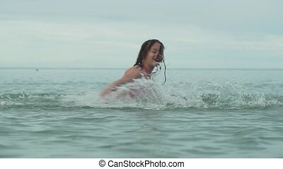 Joyful happy young girl playing with splashing water in sea slow motion stock footage video