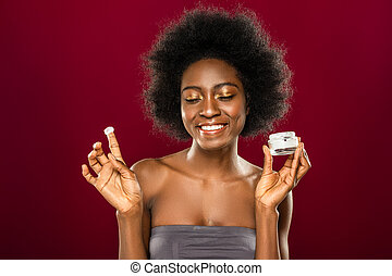 Joyful happy young woman applying facial cream