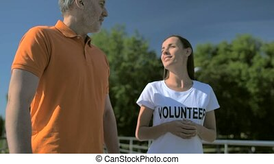 Joyful helpful female volunteer walking with a senior man -...