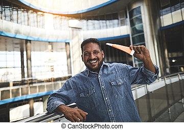Joyful Hindu man holding his id card in the airport