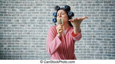 Joyful housewife with hair rollers singing in hairbrush dancing having fun