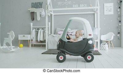 Joyful infant girl sitting in baby car at home
