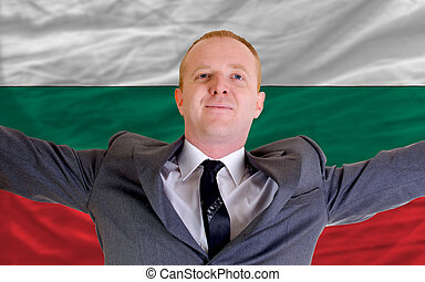 joyful investor spreading arms after good business investment in bulgaria, in front of flag