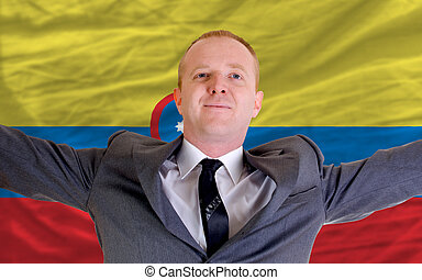 joyful investor spreading arms after good business investment in columbia, in front of flag