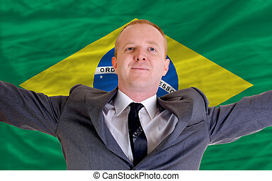 joyful investor spreading arms after good business investment in brazil, in front of flag