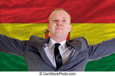 joyful investor spreading arms after good business investment in bolivia, in front of flag