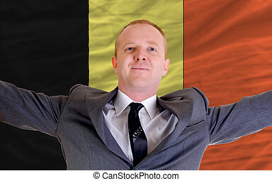 joyful investor spreading arms after good business investment in belgium, in front of flag