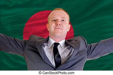 joyful investor spreading arms after good business investment in bangladesh, in front of flag