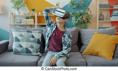 Joyful kid is having fun with augmented reality glasses gesturing wearing headset at home on sofa. Modern technology and new experiences concept.