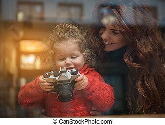Joyful kid learning how to use camera